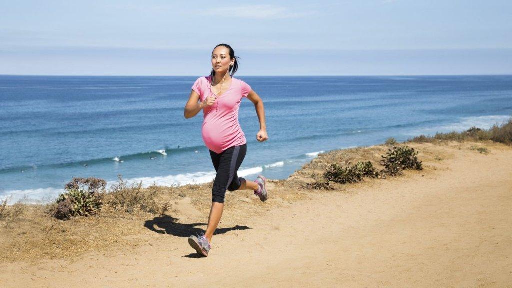mulher gravida corre na praia