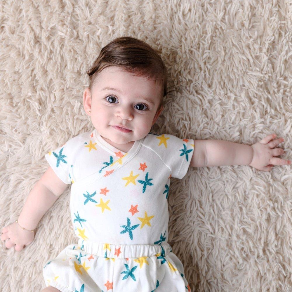 Bebê deitada no chão de body kimono trio de estrelas de algodão pima orgânico da Timirim