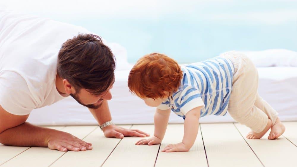 Um bebê engatinha no chão com o pai