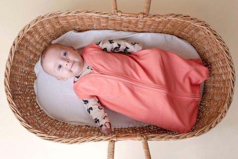 bebê com saco de dormir deitado